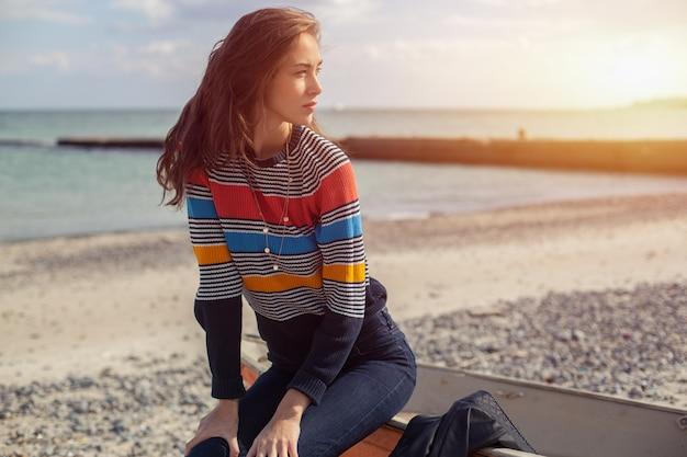 Une fille sur le côté près d'un bateau rouge sur la plage au bord de la mer