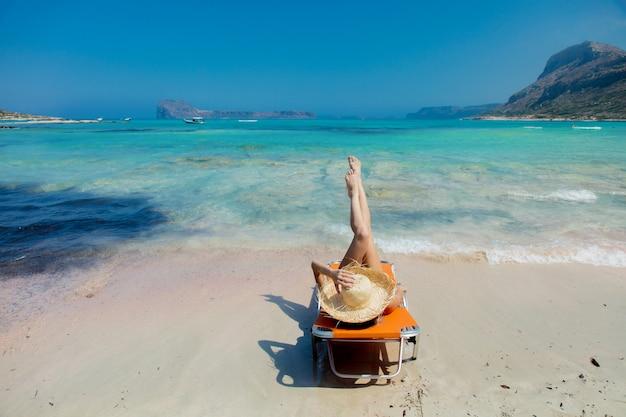 Fille couchée sur une chaise longue sur la plage de balos