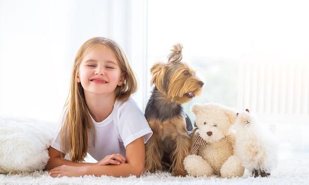 Fille couchée à côté de chien et de jouets
