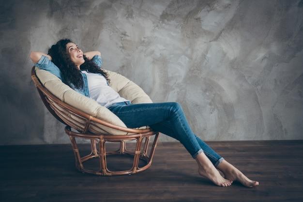 Fille couchée dans un fauteuil au repos à l'intérieur de style industriel loft moderne