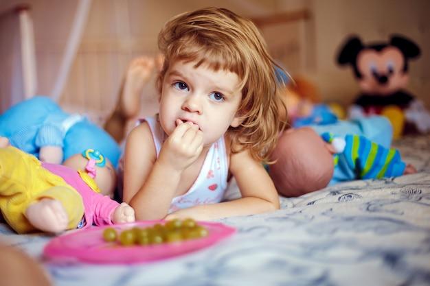 Fille couchée avec les doigts dans la bouche