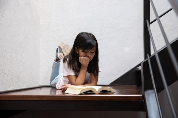 Fille couchée sur les escaliers avec mur blanc avec les pieds en haut livre de lecture avec la main sur le menton