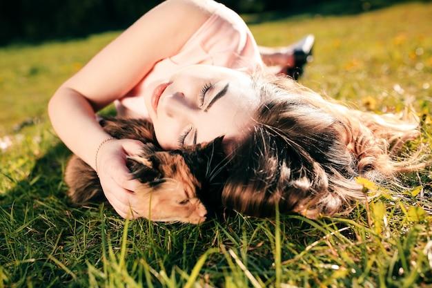 Fille couchée sur l'herbe avec chat. concept de temps chaud de printemps ou d'été.