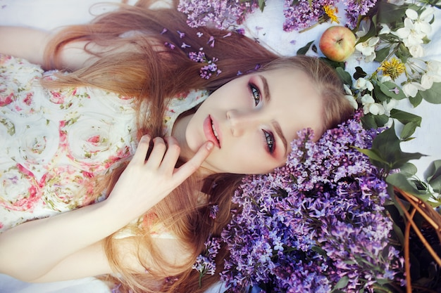 Fille couchée sur l'herbe dans les branches de fleurs lilas
