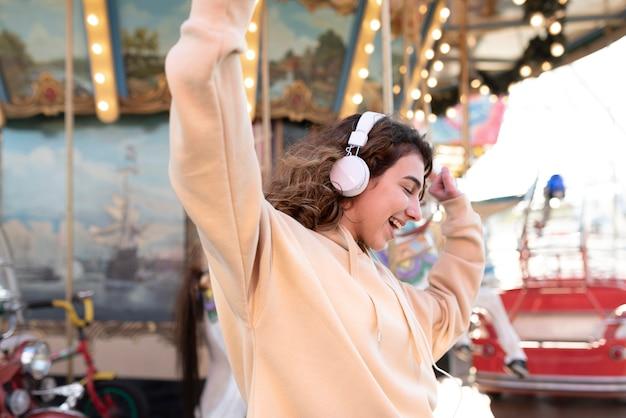 Fille de coup moyen dansant avec des écouteurs