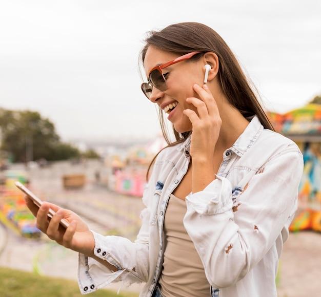 Fille de coup moyen avec écouteurs