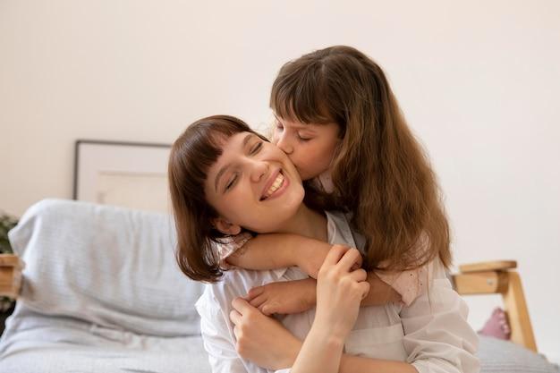Fille de coup moyen embrassant la mère