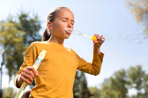 Fille de coup moyen faisant des bulles de savon