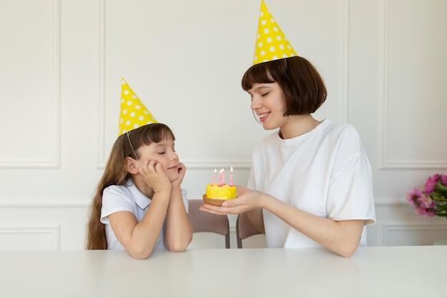 Fille de coup moyen faisant un souhait d'anniversaire
