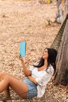 Fille de coup moyen lisant dans un hamac