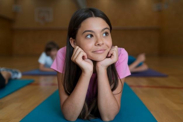 Fille de coup moyen sur un tapis de yoga