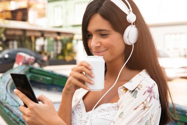 Fille de coup moyen avec téléphone et écouteurs