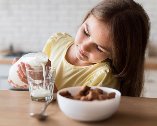 Fille de coup moyen, verser du lait