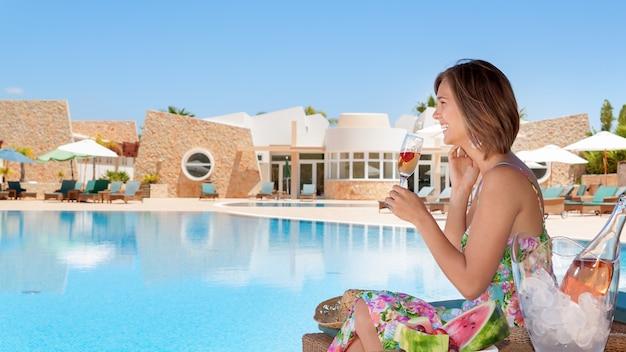 Fille avec une coupe de champagne au bord de la piscine. en été en vacances.
