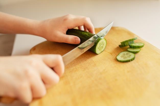 Fille coupe le concombre sur une planche de bois.