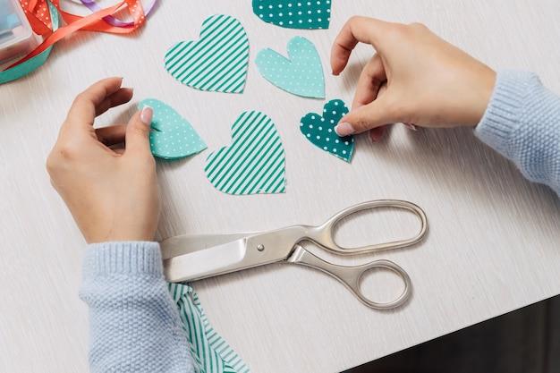La fille coupe une forme en forme de cœur à partir du tissu.