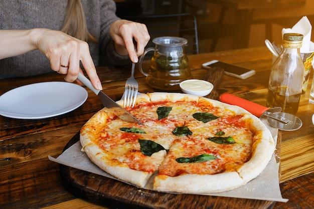 La fille coupe un morceau de pizza végétarienne avec du fromage mozzarella, des tomates, des épices et du basilic frais. délicieuse cuisine italienne. pizza margarita en tranches sur une planche de bois. fermer. délicieux déjeuner, collation