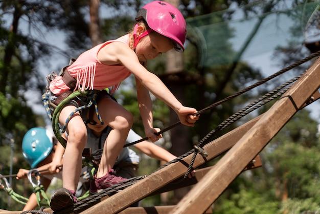 Fille courageuse s'amusant dans un parc d'aventure