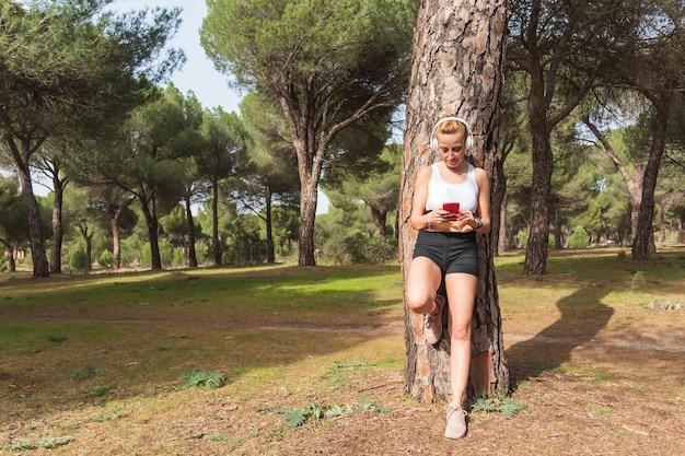 Fille de coureur de remise en forme écoutant de la musique avec des écouteurs sur un téléphone intelligent. concept de sport de technologie portable femme mode de vie actif et espace de copie.