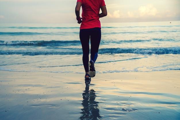 Fille courir entraînement jogging sur la plage le matin.