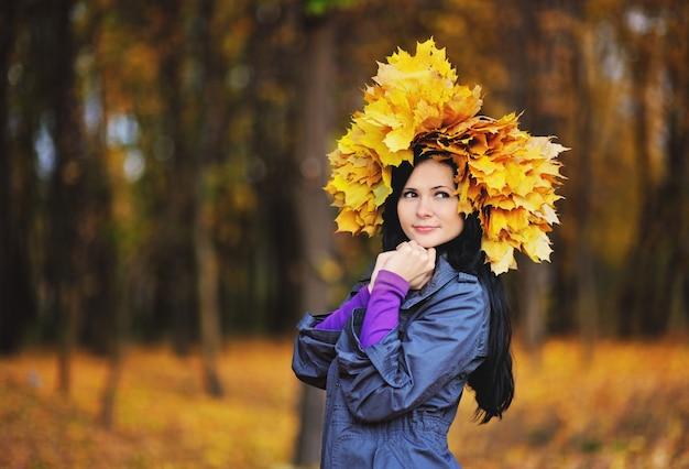 Fille avec une couronne de feuilles jaunes sur la tête sur le fond de la forêt d'automne