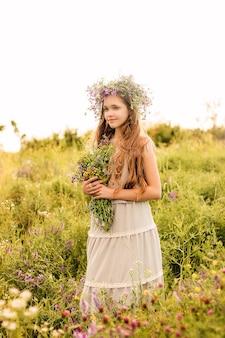 Une fille avec une couronne de fleurs sauvages sur la tête se tient dans un champ