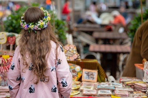 Une fille avec une couronne de fleurs se réjouit. vue de dos.