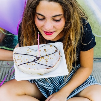 Fille avec couronne tenant une pâtisserie d'anniversaire