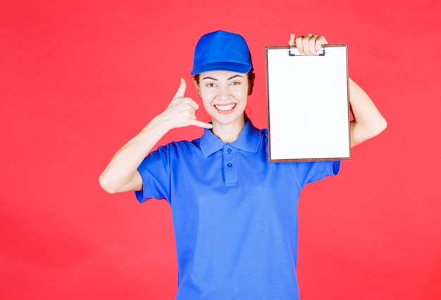 Fille de coursier en uniforme bleu tenant une liste de tâches et demandant un appel.