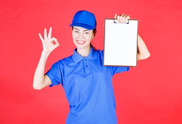 Fille de coursier en uniforme bleu tenant une liste de tâches et montrant un signe de plaisir.