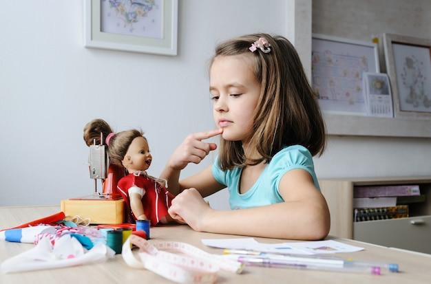La fille a cousu une nouvelle robe et l'a habillée sur une poupée.