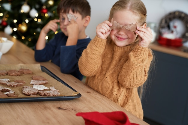 Fille couvrant les yeux avec des cookies de pain d'épice maison