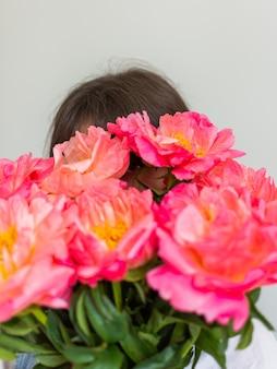 La fille couvre son visage avec un beau bouquet de pivoines roses, joyeux anniversaire ou saint valentin