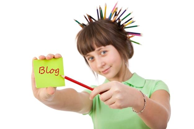 Une fille avec des crayons dans les cheveux montre sur la feuille de papier