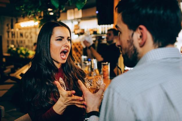La fille crie au gars. elle est malheureuse, triste et stressée. le gars essaie de se défendre.