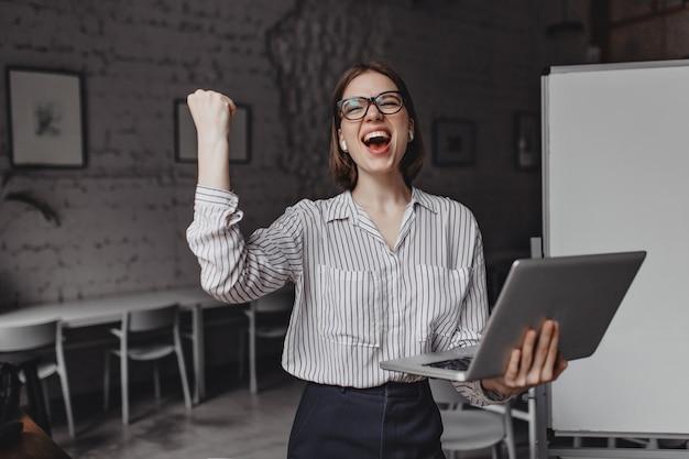 Fille crie joyeusement et fait un geste de la main gagnant, tenant un ordinateur portable et posant au bureau sur fond de tableau.