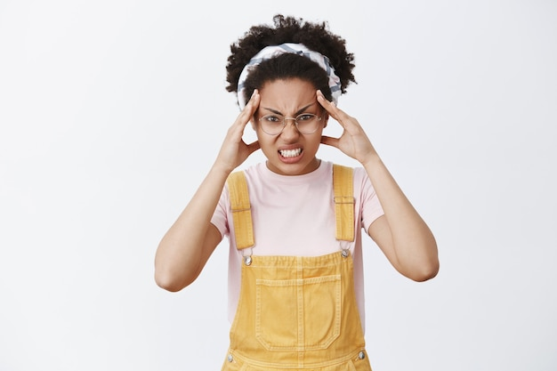 La fille croit qu'elle peut déplacer un objet avec le pouvoir de l'esprit. portrait de femme mignonne drôle et en colère en salopette, bandeau et lunettes, fronçant les sourcils et serrant les dents avec colère, tenant les doigts sur le front