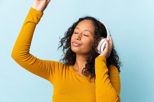 Fille cubaine adolescente isolée sur fond bleu, écouter de la musique et de la danse