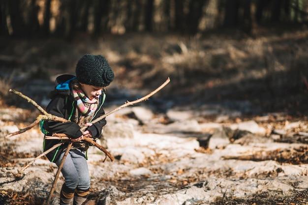 Fille de cueillir des branches dans les bois