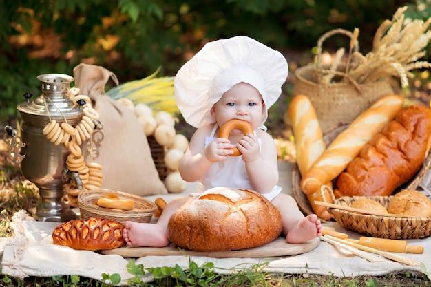 Fille cuisine dans la nature sur une journée d'été ensoleillée. le tout-petit boulanger mange du pain et des bagels dans un tablier blanc