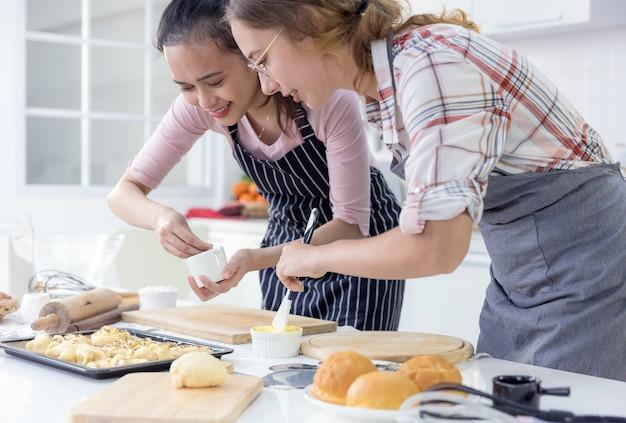 Fille de cuisson des biscuits famille les adolescentes deux multiethniques font cuire du pain