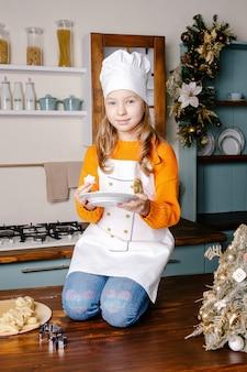 Fille cuit des biscuits pour fêter noël dans la cuisine à la maison.
