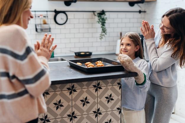 Une fille a cuit des biscuits et sa mère et son amie sont heureuses pour elle.