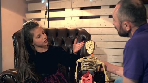 Fille curieuse posant à son père de nombreuses questions sur la structure du corps humain