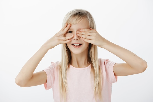 Une fille curieuse veut voir ce que son père a préparé pour le b-day. portrait de jolie fille impatiente intriguée avec de beaux cheveux blonds, couvrant les yeux avec des paumes et furtivement avec un large sourire sur mur gris