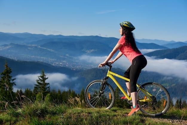Fille cycliste à cheval sur un vélo jaune sur un sentier rural dans les montagnes, profitant de la brume matinale dans la vallée, les forêts sur l'arrière-plan flou