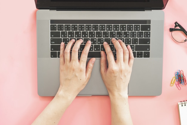 Fille, dactylographie, sur, ordinateur portable, dans, rose, pastel, bureau coloré, à, accessoires