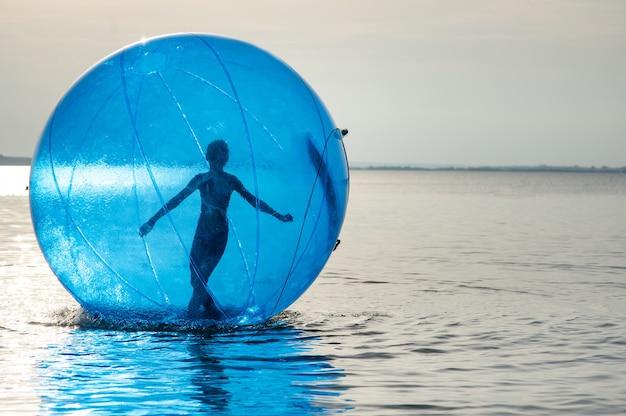Une fille dans une attraction gonflable sous forme de boule sur la mer