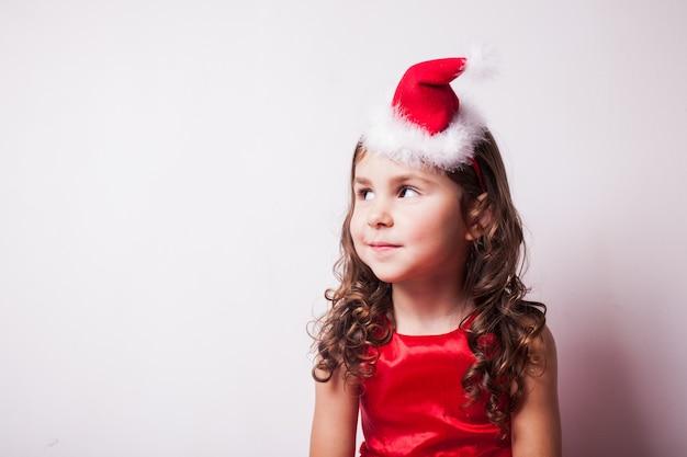 Fille dans le bandeau de chapeau de santa sur le mur blanc, espace de copie