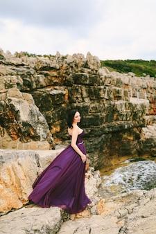 Fille dans une belle robe lilas flottant au vent se dresse sur un rocher sur fond de